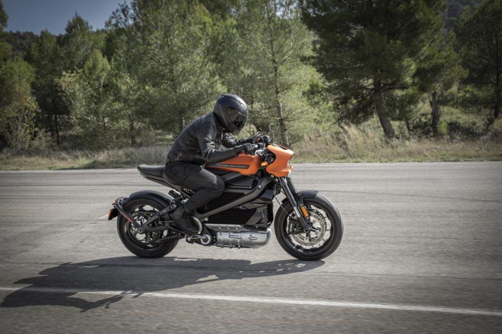 Um motoqueiro sobre uma moto elétrica cor de laranja em uma estrada
