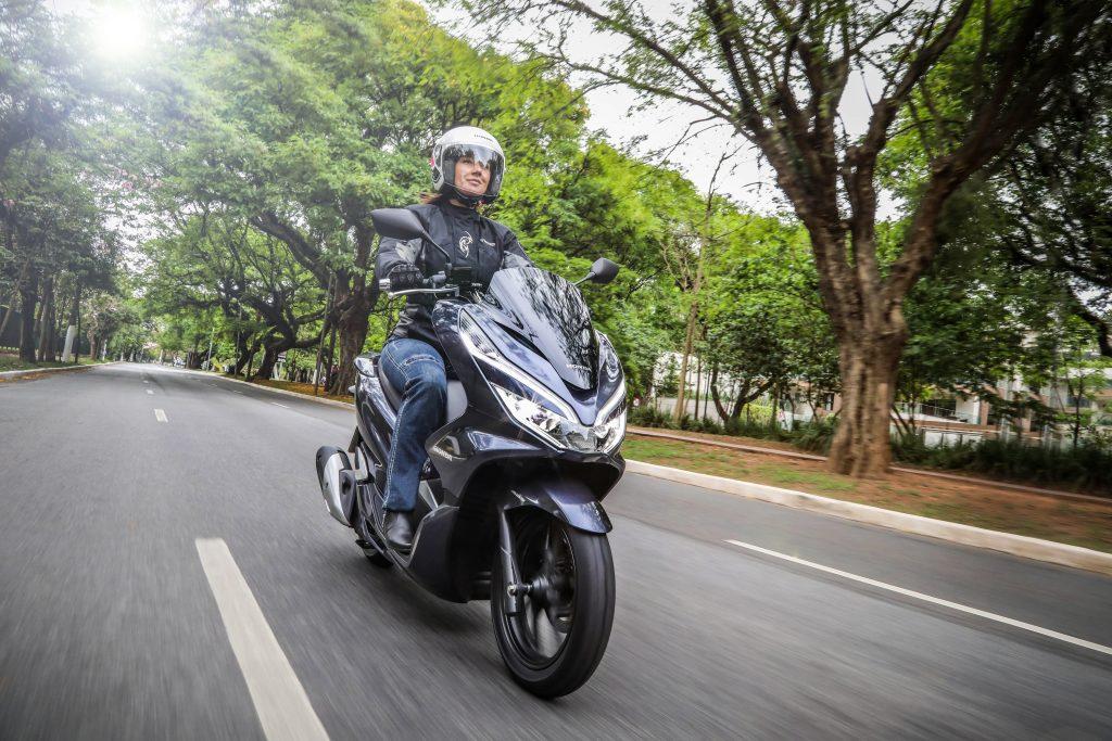 mulher pilota scooter em avenida arborizada