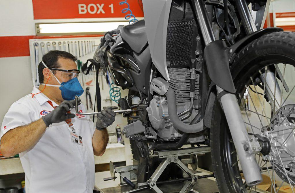 mecanico faz manutenção em moto honda